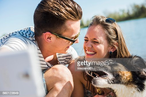 Happy young couple taking selfie with dog by the riverside