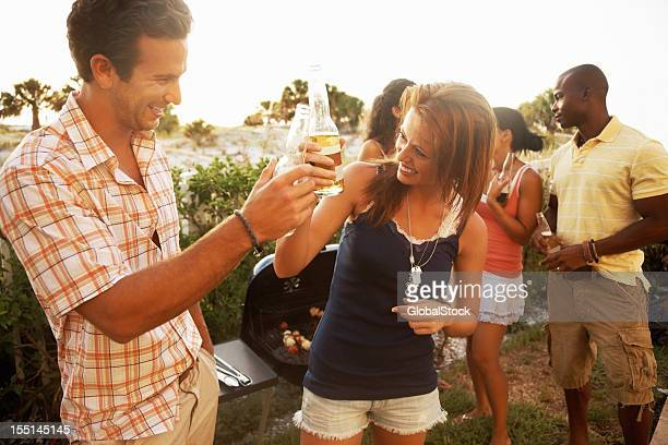 Happy young couple toasting beer with friends in background