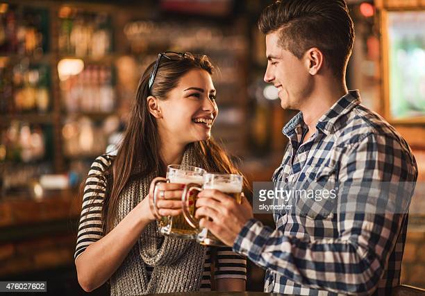 Happy young couple toasting with beer in a bar.