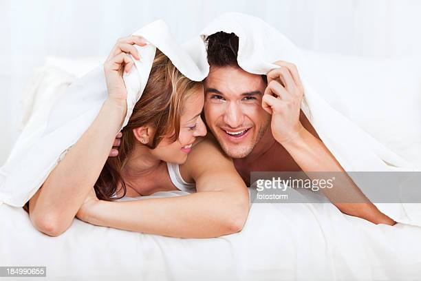 Happy young couple under covers in bed