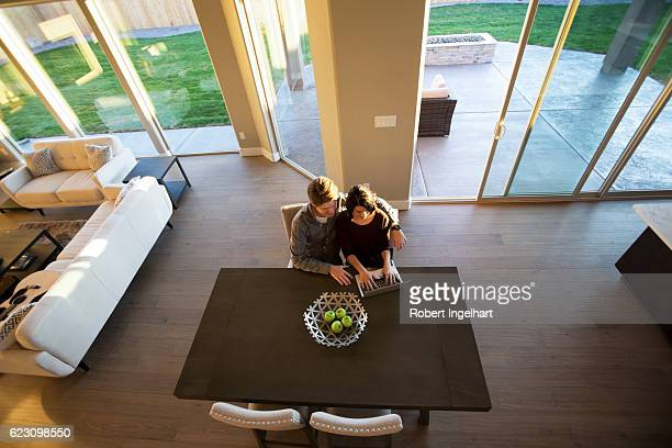 Happy Young Couple Using Laptop in New Home with Sunflares