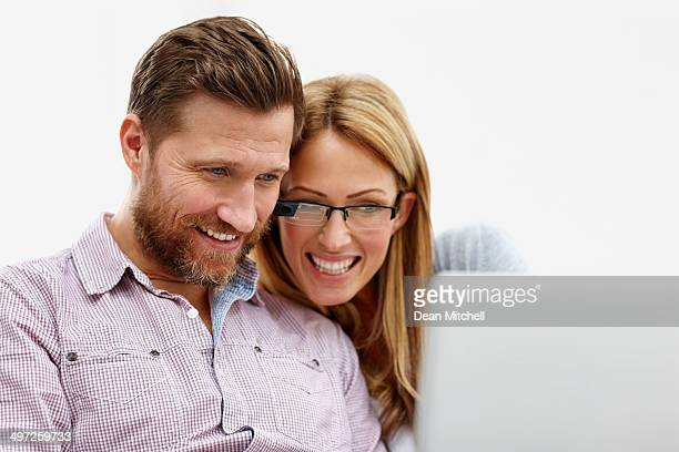 Happy young couple using laptop together