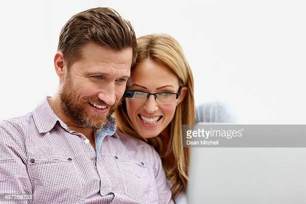 Heureux jeune couple à l'aide d'ordinateur portable ensemble