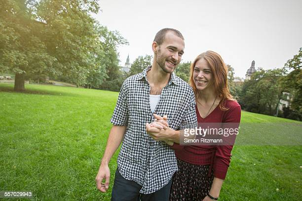 Happy young couple walking in park