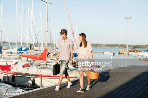 Happy young couple walking together on pier