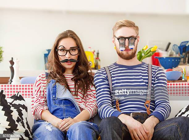 Happy young couple wearing funny masks