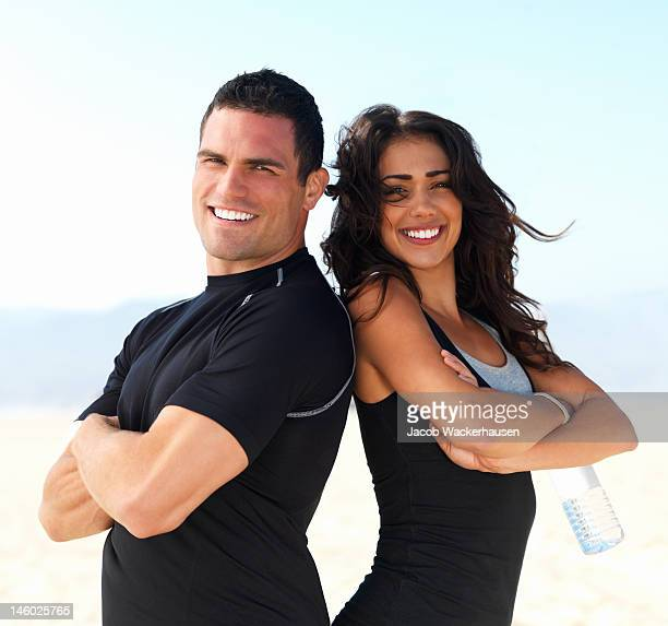 Happy young couple with arms crossed