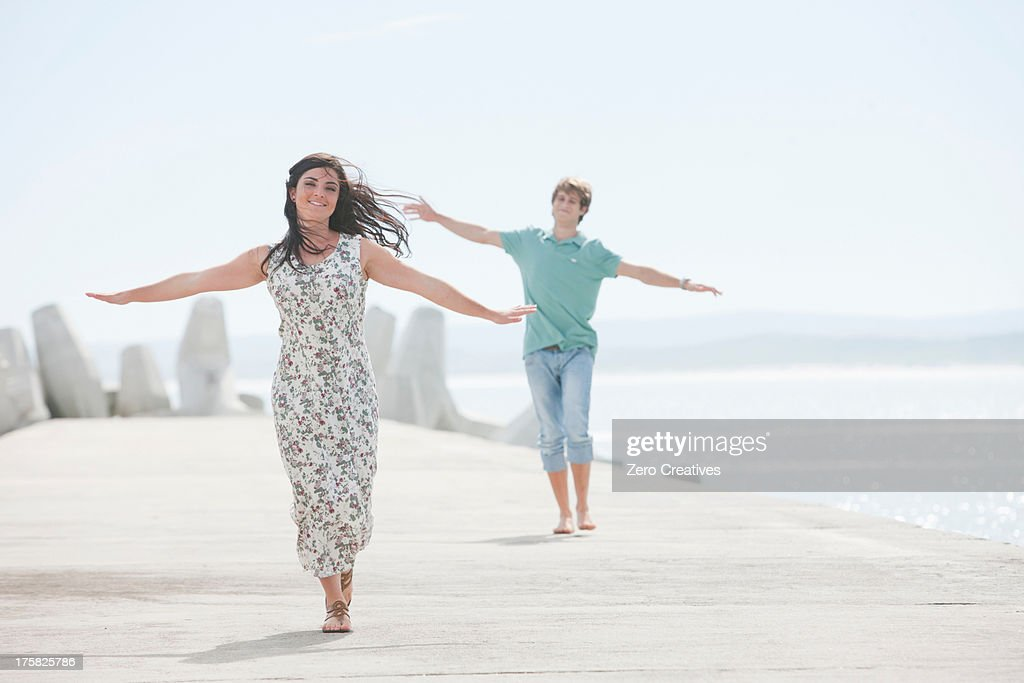 Happy young couple with arms outstretched on pier : Stock Photo