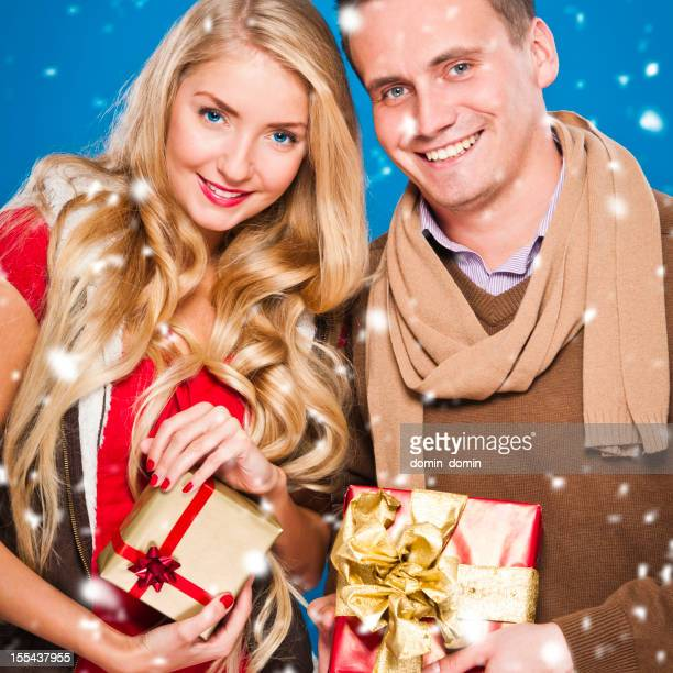 Happy young couple with Christmas gifts smiling, it's snowing