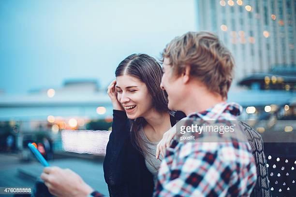 幸せな若いカップルに、スマートフォン、東京でアウトドア