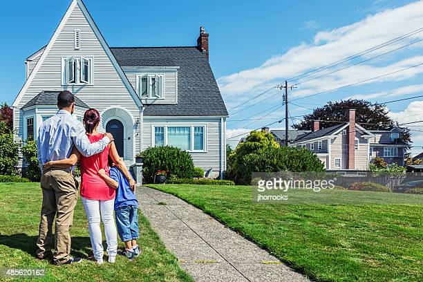 Happy Young Family Admiring Home