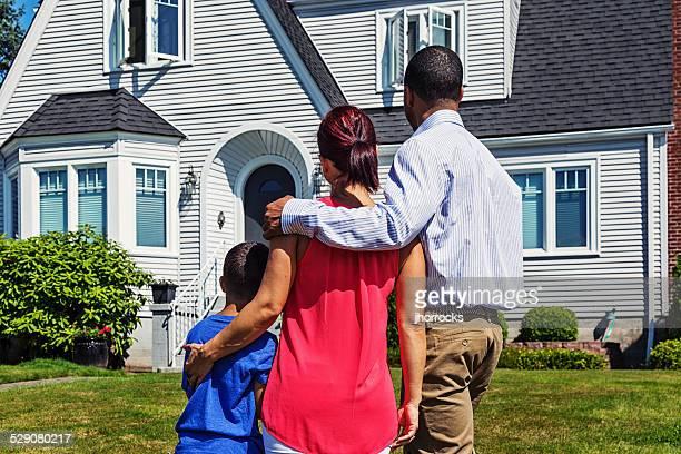 Felice giovane famiglia davanti a casa