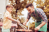 Father and son having a barbecue party in their garden.