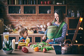 Happy young family, beautiful mother with two children, adorable preschool boy and baby in sling cooking together in a sunny kitchen. Vintage style.
