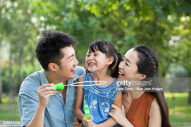 Happy young family blowing bubbles