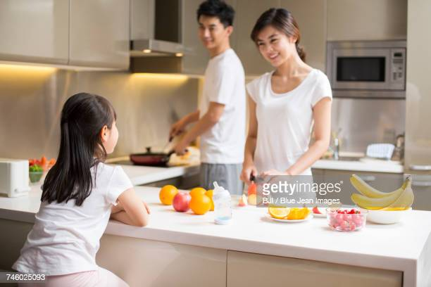 Happy young family cooking in kitchen
