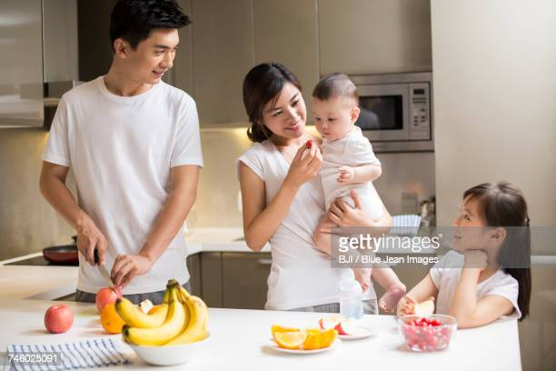 Happy young family eating fruit in the kitchen