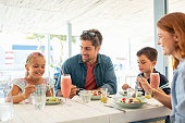 Cheerful family in restaurant enjoying lunch together in a patio. Mother and father observing daughter while eating food with son busy in eating. Smiling family with two children eating brunch togethe