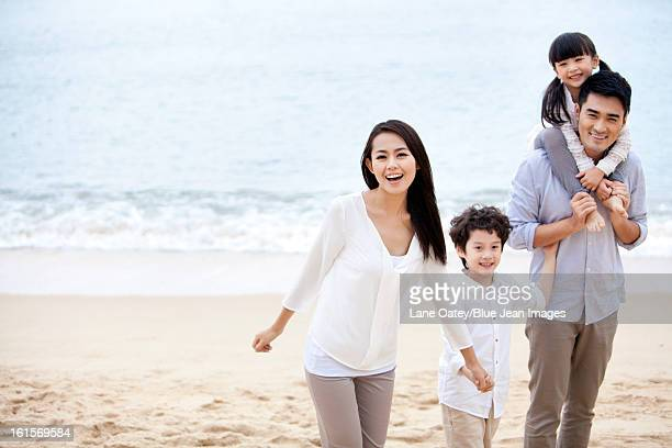 Happy young family having a good time on the beach of Repulse Bay, Hong Kong