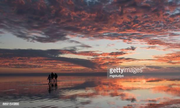 Happy young family having fun running on salt lake at sunset