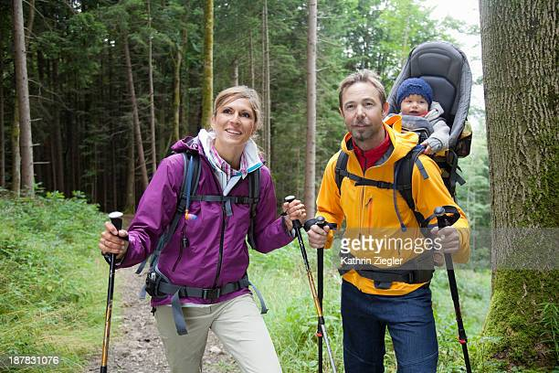 happy young family hiking, girl in baby carrier
