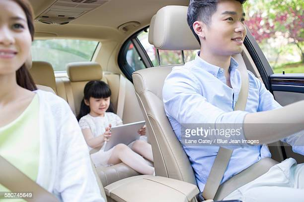 Happy young family in a car