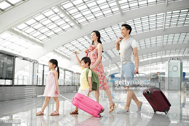 Happy young family leaving with luggage