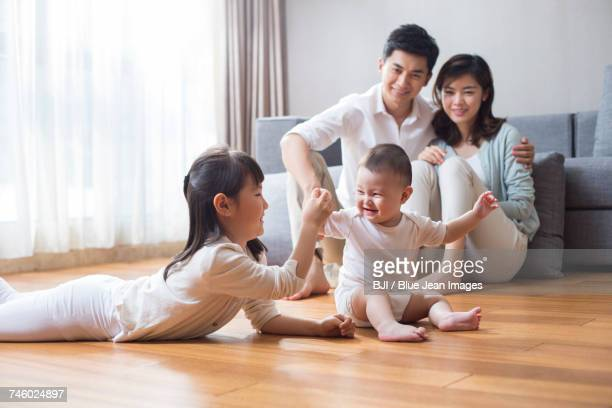 Happy young family lying on wooden floor