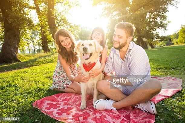 Glückliche junge Familie an einem Sommertag mit Ihrem Hund