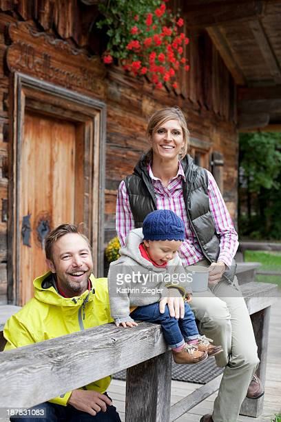 happy young family outside chalet, drinking tea