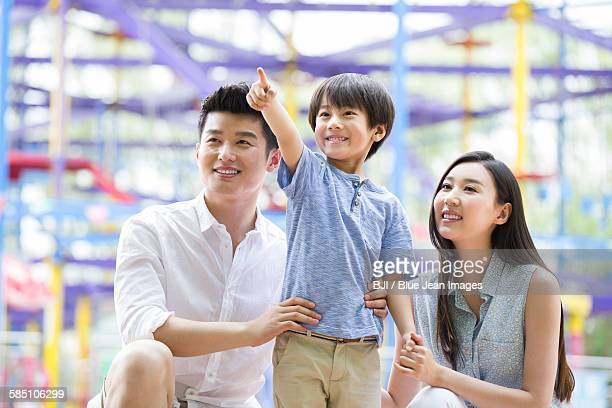 Happy young family playing in amusement park