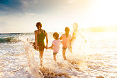 happy young family playing on beach at sunset