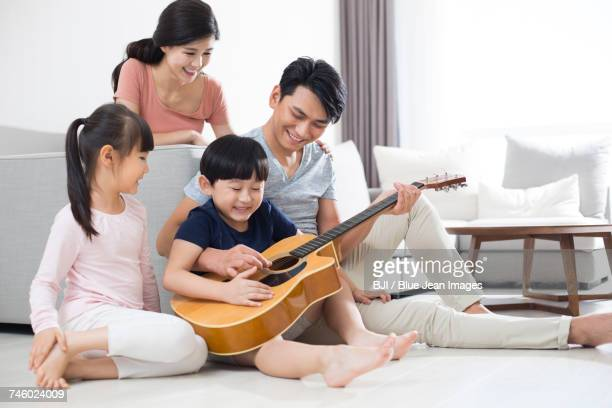 Happy young family playing the guitar at home