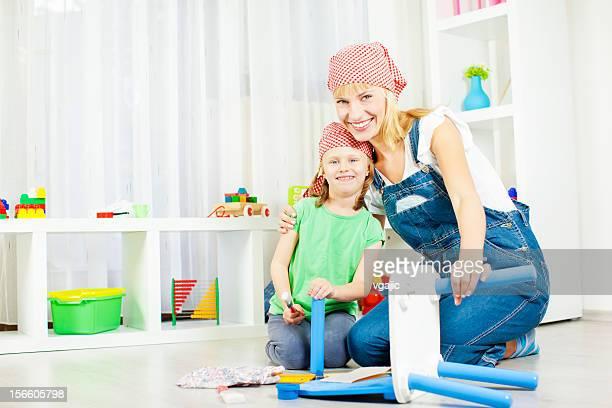 Glückliche junge Familie Reparatur Möbel wie zu Hause fühlen.