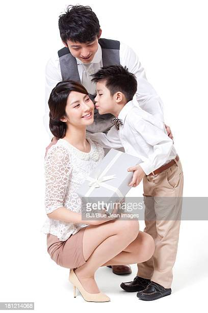 Happy young family sending gift and kissing