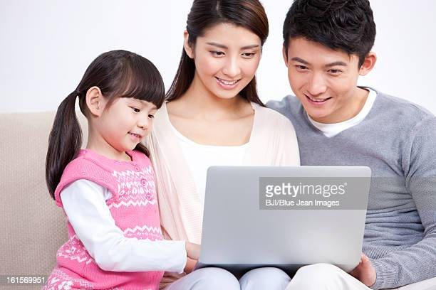 Happy young family sitting in sofa and sharing a laptop