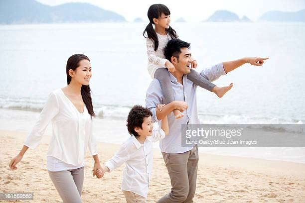 Happy young family strolling on the beach of Repulse Bay, Hong Kong