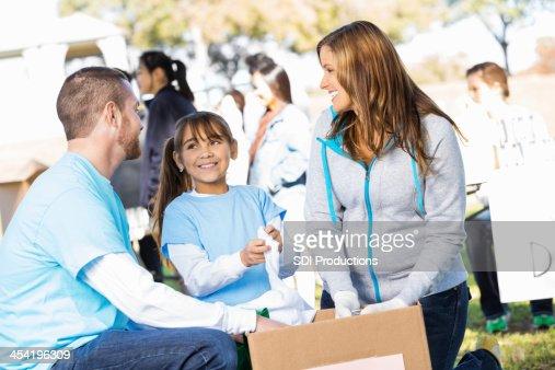 Trabajo voluntario para la familia joven feliz juntos en la donación drive : Foto de stock