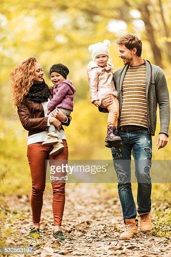 Felice giovane famiglia a piedi nella foresta.