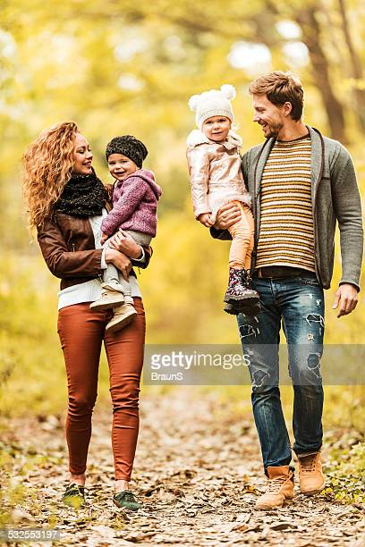 Happy young family walking in forest.