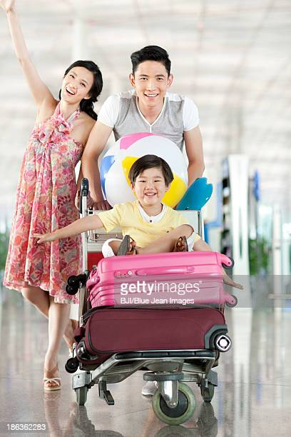 Happy young family with luggage cart at the airport