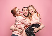Happy young family with one little daughter posing together on pink studio background