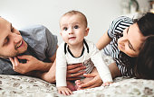 Happy young father, mother and cute baby boy lying on bed