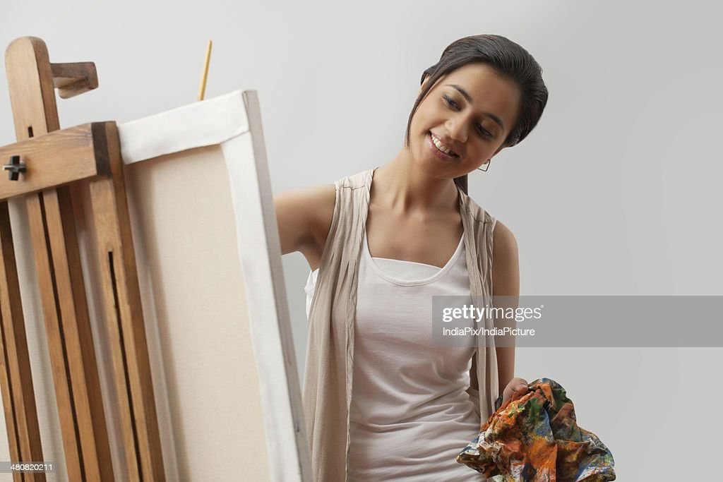 Happy young female artist painting on canvas over gray background : Stock Photo