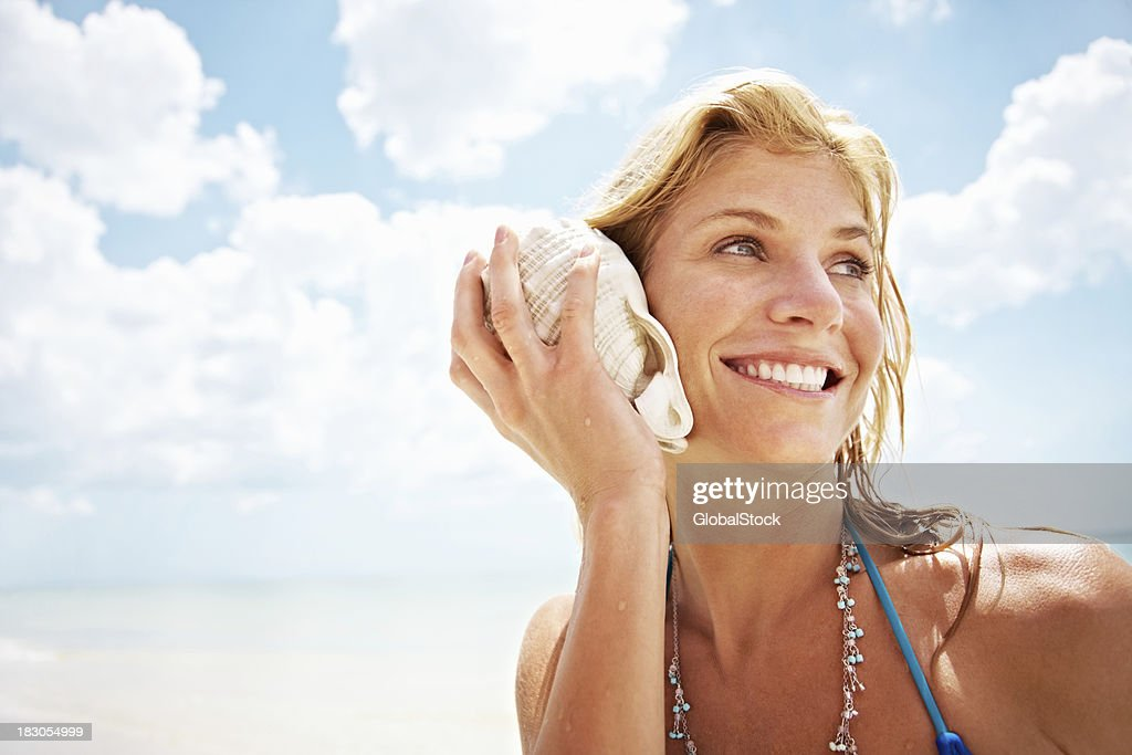 Happy young female holding a conch shell against sky