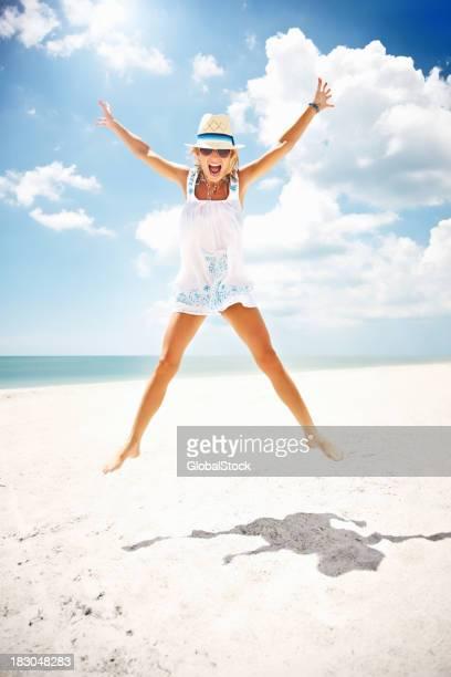 Glückliche junge Frau springt über die Ausgestreckte Arme am Strand
