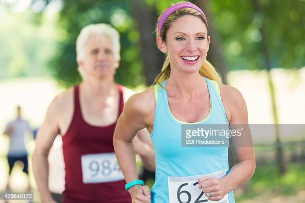 Happy young female runner in marathon or charity 5k race