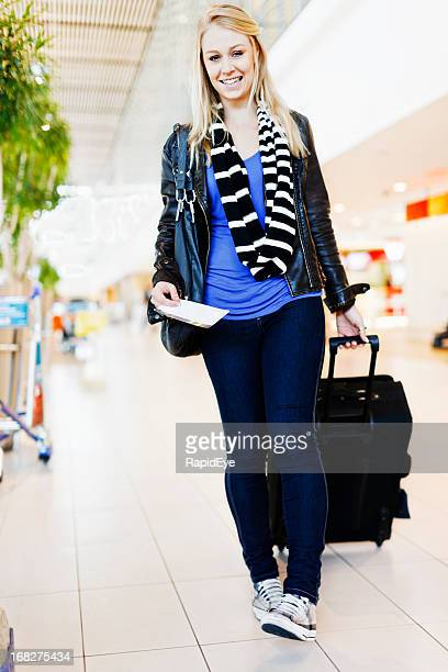 Happy young female traveler pulling suitcase through airport concourse