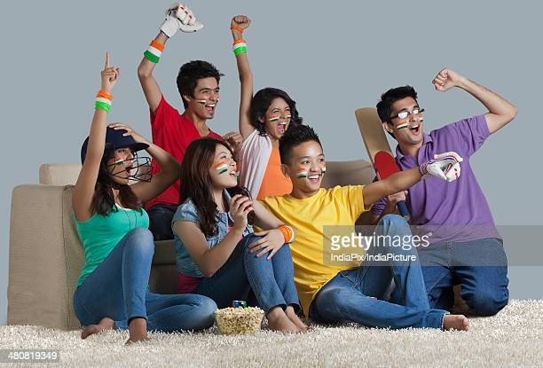 Happy young friends cheering while watching cricket match at home