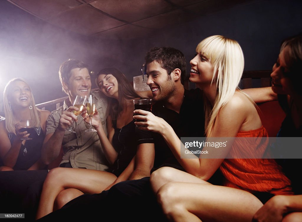 'Happy, young friends enjoying their drinks at a night club'